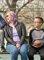 A mother and her two children with chronic granulomatous disease (CGD) sitting on a bench